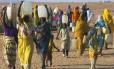 Dafur, no Sudão: Mulheres carregam água sobre as cabeças tirada de poço construído pela Oxfam