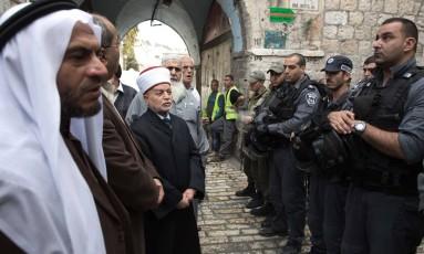 Policiais israelenses impedem o líder religioso Mohammed Hussein (centro) de entrar na mesquita al-Aqsa, na cidade velha de Jerusalém Foto: MENAHEM KAHANA / AFP