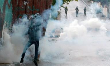 Palestino atira bomba de gás lacrimogêneo contra forças de segurança israelenses durante confrontos no campo de refugiados de Aida, perto da cidade Cisjordânia Foto: MUSA AL-SHAER / AFP