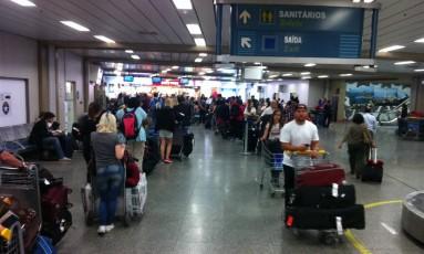 Fila de passageiros para passar pela Receita Federal, na área de desembarque do Aeroporto Internacional Tom Jobim Foto: O Globo / Laura Antunes