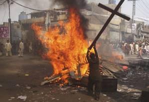 Paquistanês queima cruz em protesto Foto: Reuters
