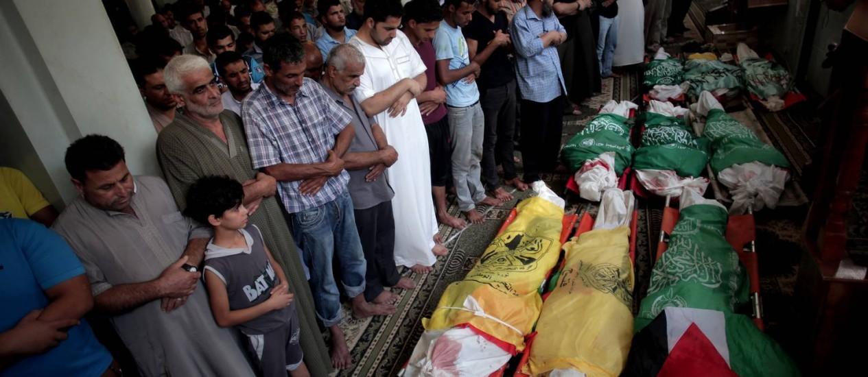 Palestinos velam corpos de familiares mortos em ataque israelense, em julho passado Foto: AP/Khalil Hamra