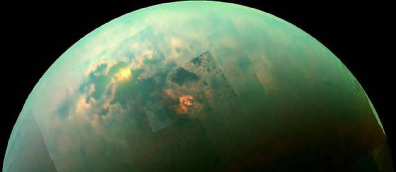 Raios solares refletem sobre o gelo e as águas frias de Titã Foto: Nasa