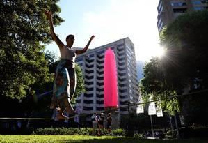 Menina pratica slackline no Hyde Park, em Sydney, na Austrália, em frente a obelisco envelopado por camisinha gigante Foto: SAEED KHAN / AFP