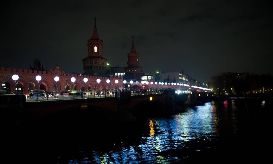 """Os balões do projeto """"Fronteira de Luz"""" ('Lichtgrenze 2014') são refletidos no rio em Oberbaumbruecke in Berlin. A instalação com 8 mil balões luminosos celebra os 24 anos da queda do Muro de Berlim Foto: Steffi Loos / AP"""