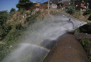A água que anda escassa na Bacia do Paraíba do Sul jorra com fartura de um cano furado no Morro da Cachoeirinha, no Lins Foto: Marcelo Carnaval / Agência O Globo
