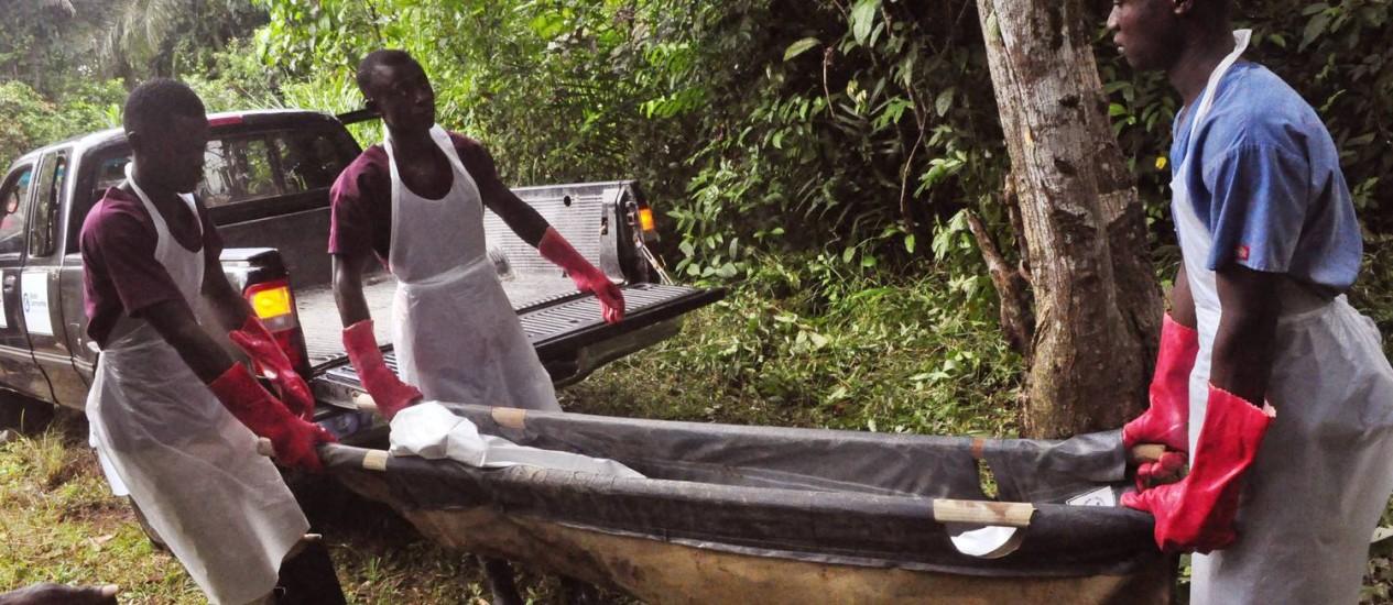 EM SEGURANÇA. Profissionais enterram o corpo de uma vítima do ebola em Monróvia, na Libéria Foto: Abbas Dulleh / Abbas Dulleh/AP