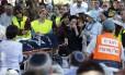Brenda Lemkus chora ao lado do corpo de sua filha Dalia durante seu funeral no assentamento israelense de Tekoa, na Cisjordânia