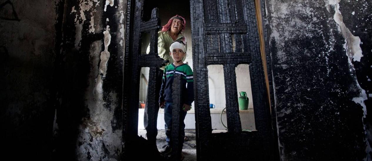 Palestinos inspecionam danos de uma mesquita incendiada na aldeia da Cisjordânia de Mughayer, ao norte de Ramallah Foto: Majdi Mohammed / AP