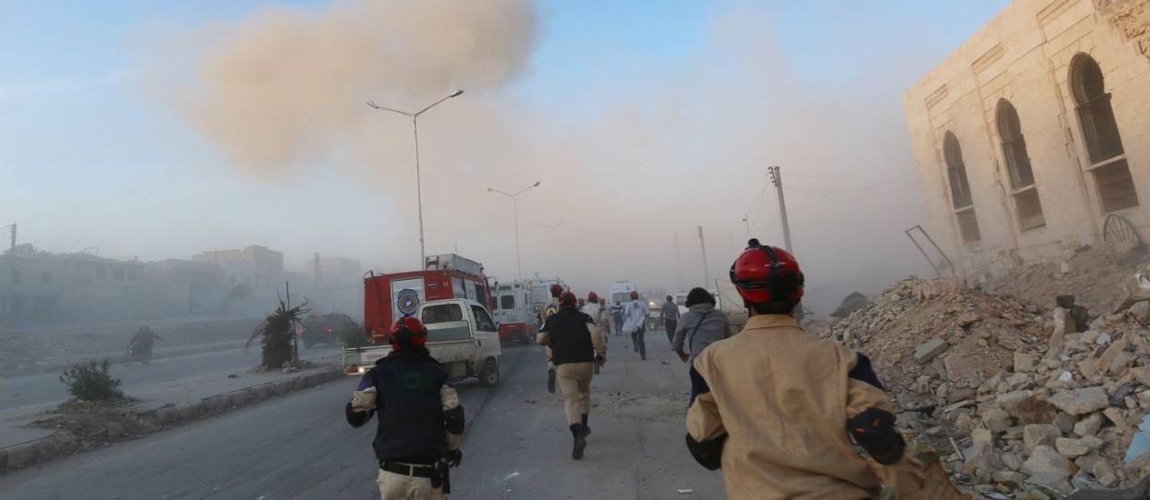 Membros da Defesa Civil síria correm em Aleppo após um bombardeio Foto: ZEIN AL-RIFAI / AFP