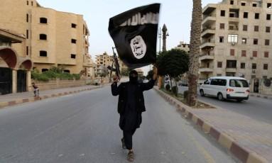 Um membro do Estado Islâmico segura uma bandeira do grupo extremista na cidade síria de Raqqa Foto: STRINGER / REUTERS