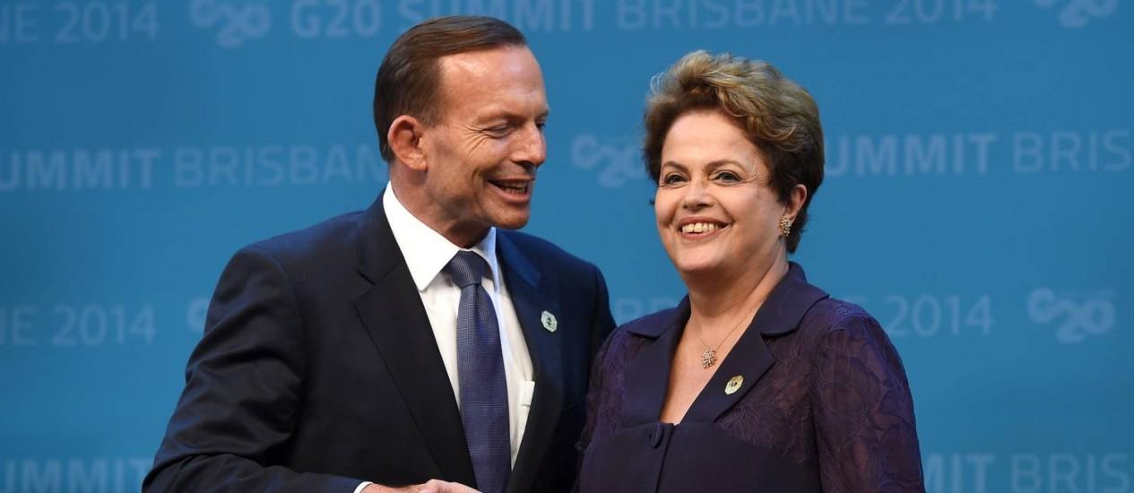 O primeiro-ministro da Austrália, Tony Abbott, dá as boas-vindas à presidente Dilma no encontro do G20. Em seu primeiro discurso diante de líderes mundiais, a presidente não falou sobre o rumo que pretende dar à economia brasileira, segundo um participante Foto: AFP