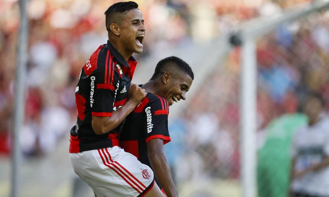 Everton sobe nas costas de Gabriel para festejar o gol que marcou pelo Flamengo após linda jogada do companheiro Foto: Guito Moreto / Agência O Globo