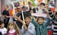 Crianças seguram cartazes em protesto contra o genocídio dos yazidis no Iraque