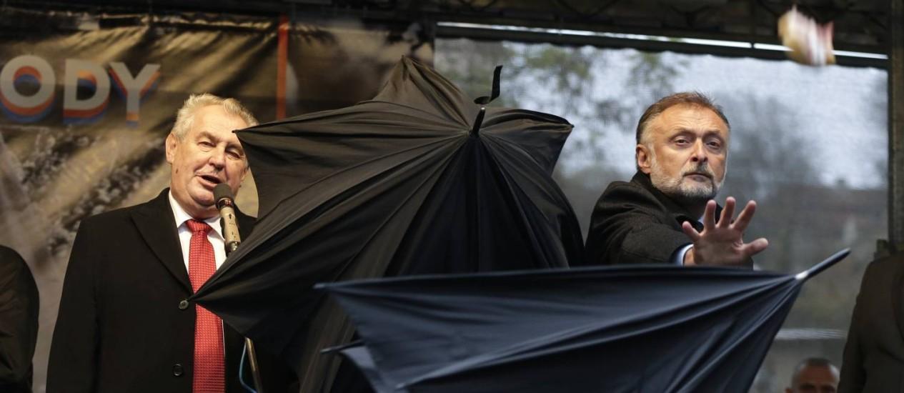 Seguranças tentam proteger o presidente Milos Zeman com guarda-chuvas, enquanto manifestantes atiram ovos, tomates e até sanduíches durante protesto em 2014 Foto: Petr David Josek / AP
