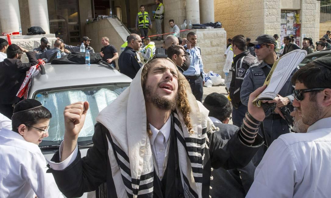 Judeu ultra-ortodoxo reza no local de um ataque realizado por dois palestinos contra uma sinagoga em Jerusalém Foto: JACK GUEZ / AFP