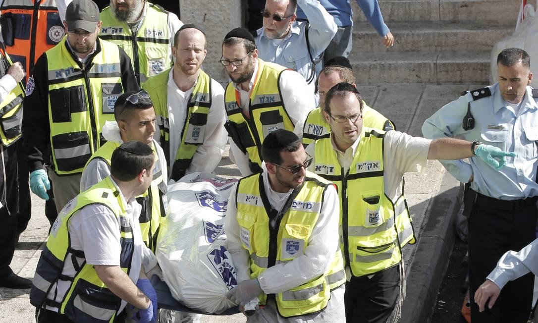 Membros dos serviços de emergência israelenses transportam um corpo do local do atentado, no bairro ultra-ortodoxo Har Nof Foto: AHMAD GHARABLI / AFP