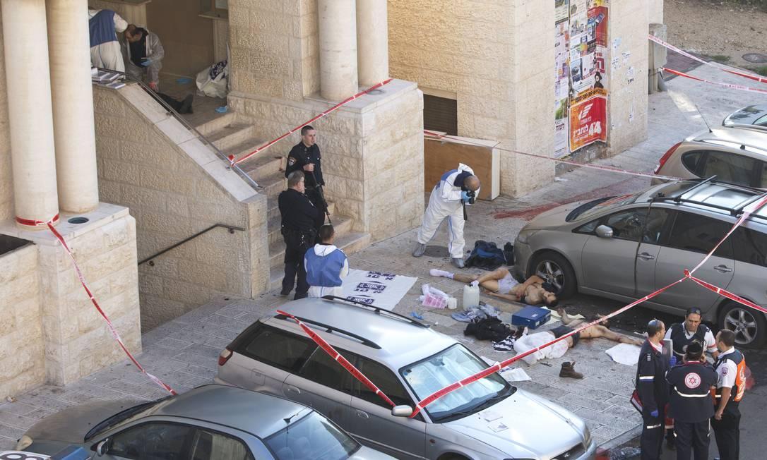 Especialistas fotografam corpos de dois palestinos mortos pela polícia após realizaem um ataque em Jerusalém Foto: Sebastian Scheiner / AP