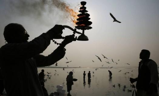 Um sacerdote hindu gira uma lâmpada a óleo, durante as orações da manhã nas margens do rio Ganges, em Allahabad, na Índia Foto: Rajesh Kumar Singh / AP