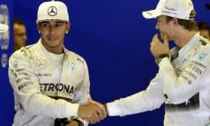 Lewis Hamiton e Nico Rosberg apertam as mãos após o treino classificatório, na véspera da prova decisiva do Mundial Foto: Tom Gandolfini / AFP