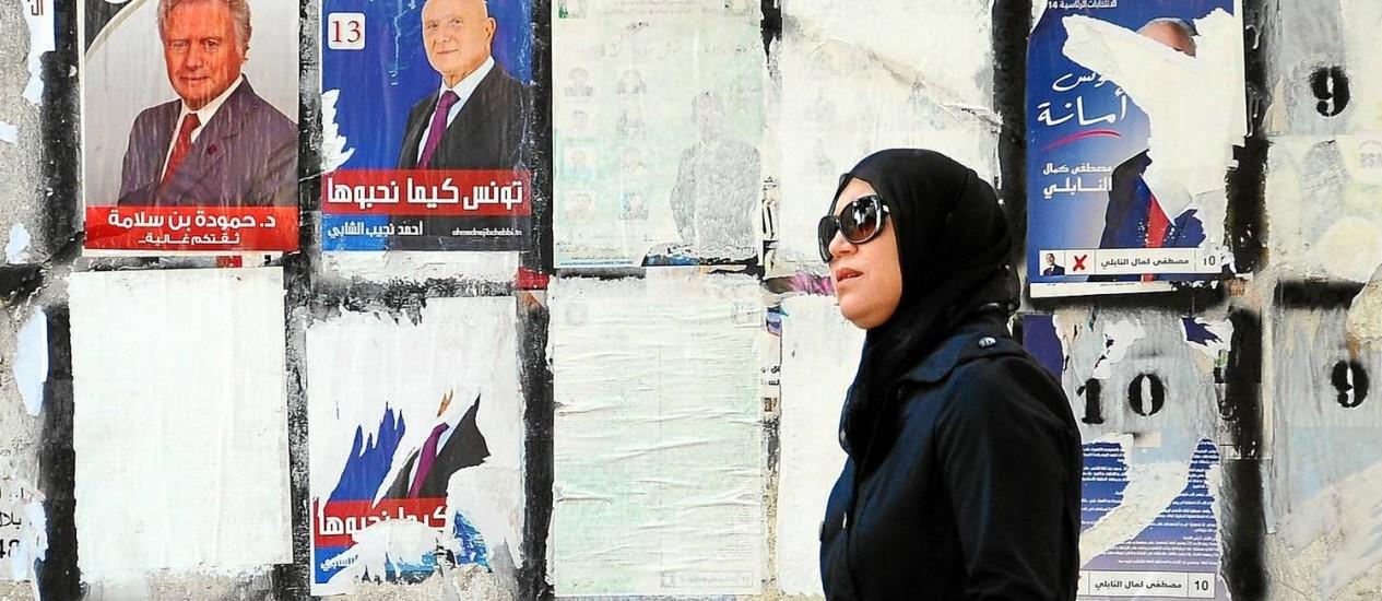 Mulher tunisiana passa por muro com propagandas de candidatos à Presidência em Túnis: país é visto como oásis de sucesso na Primavera Árabe Foto: Hassene Dridi/AP