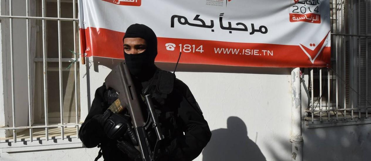Um policial tunisiano monta guarda em frente à sessão eleitoral antes da eleição presidencial, na cidade de Beja Foto: FADEL SENNA/AFP