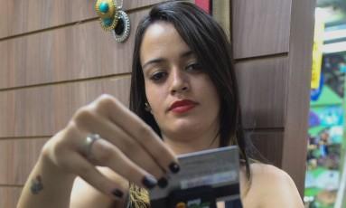 A loja em que a vendedora Alana Pinheiro trabalha, em Brasília, usa leitora de cartão acoplada ao smartphone Foto: André Coelho / Fotos de André Coelho