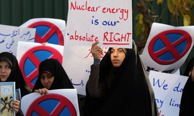"""Iraniana segura cartaz dizendo """"A energia nuclear é nosso direito absoluto"""" durante uma manifestação em Teerã Foto: ATTA KENARE / AFP"""