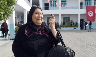 Mulher mostra dedo sujo de tinta após votar em primeira eleição livre para presidente da era pós-Ben Ali, na capital Túnis Foto: FETHI BELAID / AFP