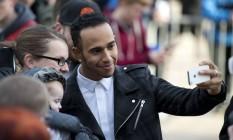 Hamilton tira um selfie com uma fã na Inglaterra. Bicampeão está perto de renovar contrato com a Mercedes Foto: OLI SCARFF / AFP