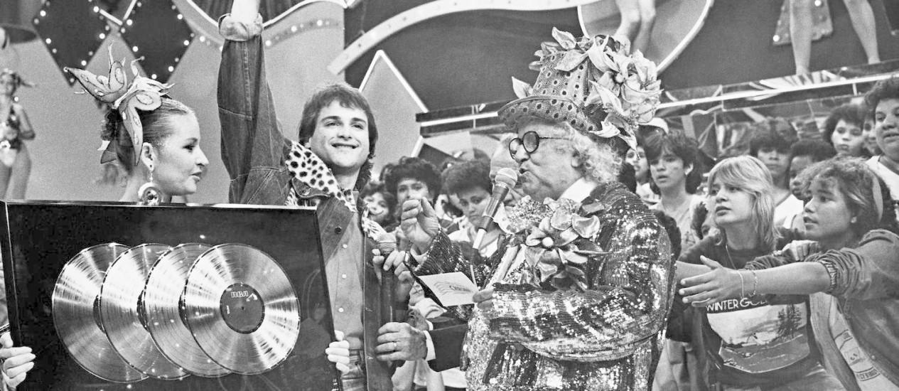 Chacrinha, em seu 'Cassino', em pleno auge do BRock dos anos 1980, entregando disco de ouro a Sylvinho Blau Blau Foto: Divulgação