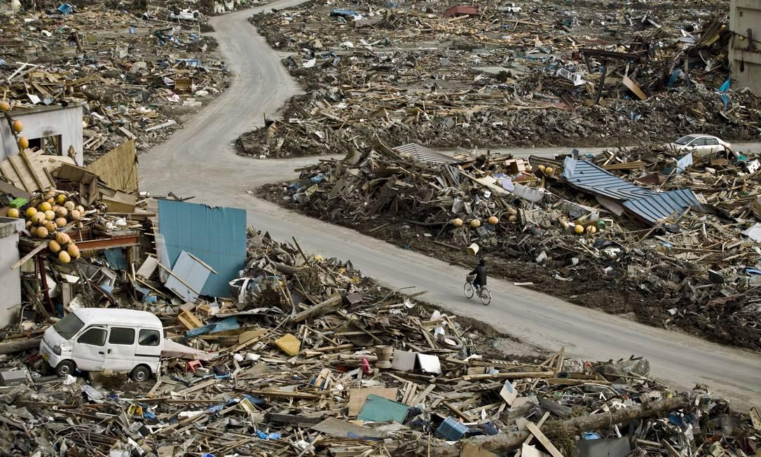 Ciclista passeia por área devastada em Otsuchi, no Japão, depois de terremoto em 2011 Foto: Shiho Fukada/The New York Times /