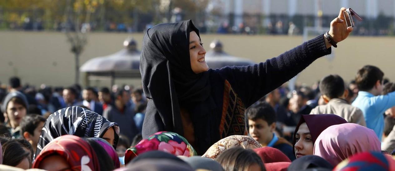 Menina faz uma selfie enquanto aguarda por inauguração de escola com o presidente Tayyip Erdogan: muçulmanos têm sido bastante contemplados por novas políticas do governo turco Foto: UMIT BEKTAS / REUTERS