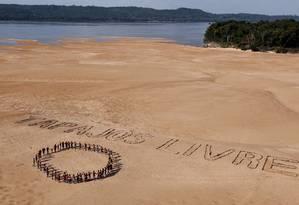 """Ativistas do Greenpeace e índios Mundukuru usam pedras para formar a frase """"Tapajós Livre"""" nas areias às margens do rio de mesmo nome, próximo a Itaituba, no Pará Foto: Divulgação/Marizilda Cruppe/Greenpeace"""