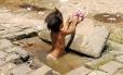 A menina no buraco com água suja: alheio à situação, o pai só se preocupava em pedir dinheiro para almoçar