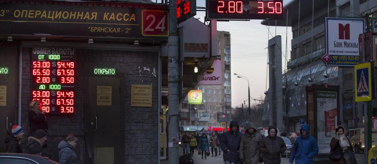 Russos passam por um display com várias taxas de câmbio perto da estação ferroviária de Kiev, em Moscou Foto: Alexander Zemlianichenko / Alexander Zemlianichenko/AP