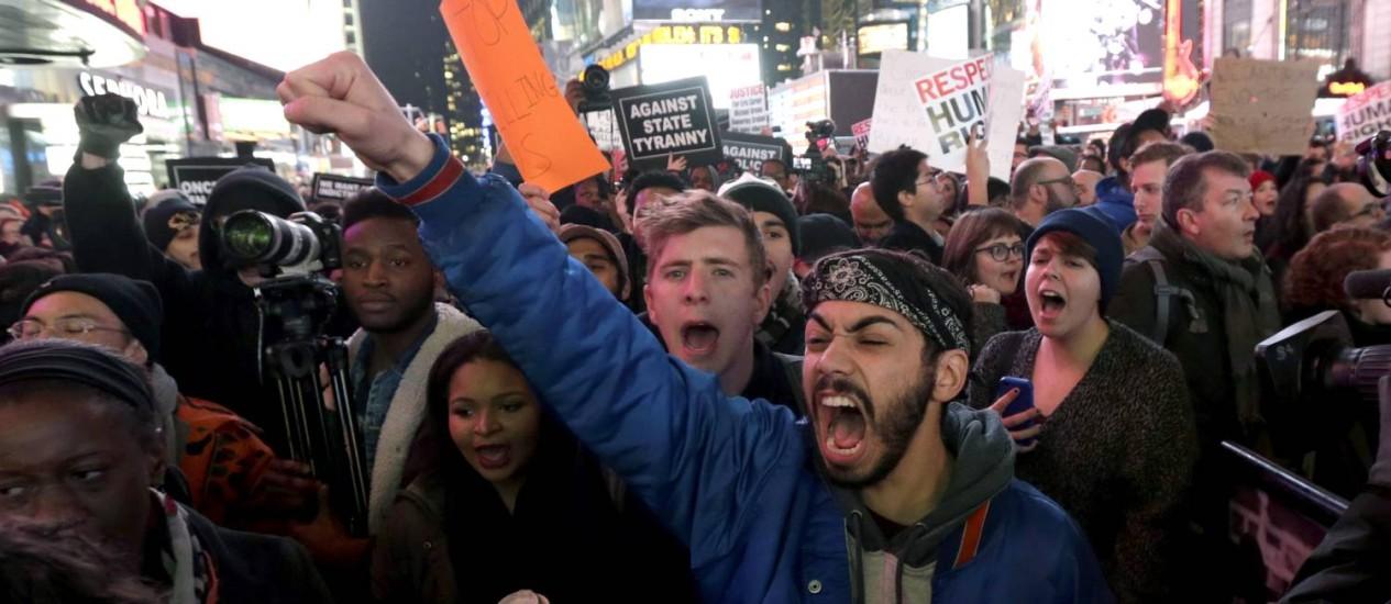 Manifestantes na Times Square protestam contra a decisão do grande júri que não indiciou o policial Daniel Pantaleo que aplicou manobra proibida, matando o camelô Eric Garner Foto: Julio Cortez / AP