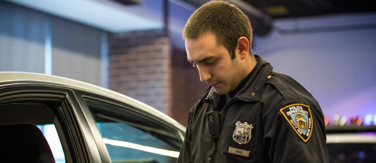 Policial demonstra funcionamento da câmera portátil Foto: Andrew Burton / AFP
