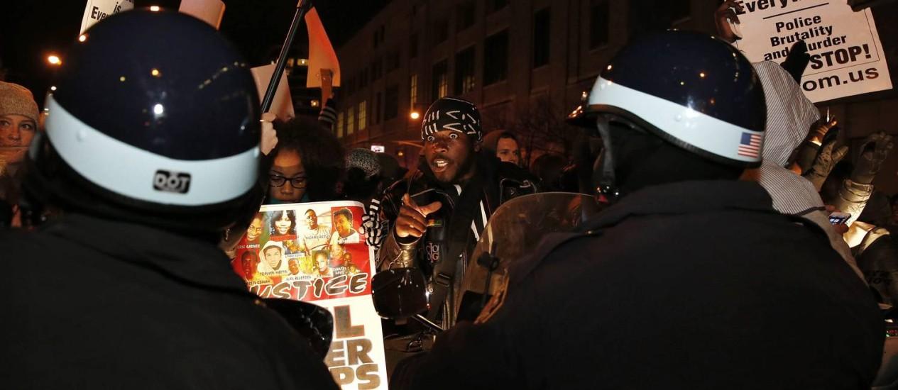Manifestantes com cartazes fazendo referência a Ferguson confrontam policiais em Manhattan Foto: SHANNON STAPLETON / REUTERS