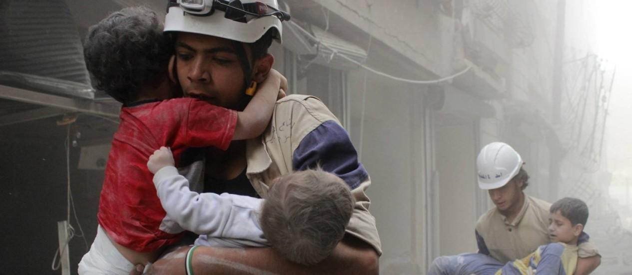 Membros da defesa Civil resgatam crianças após ataque na cidade síria de Aleppo Foto: SULTAN KITAZ / Reuters/8-12-2014