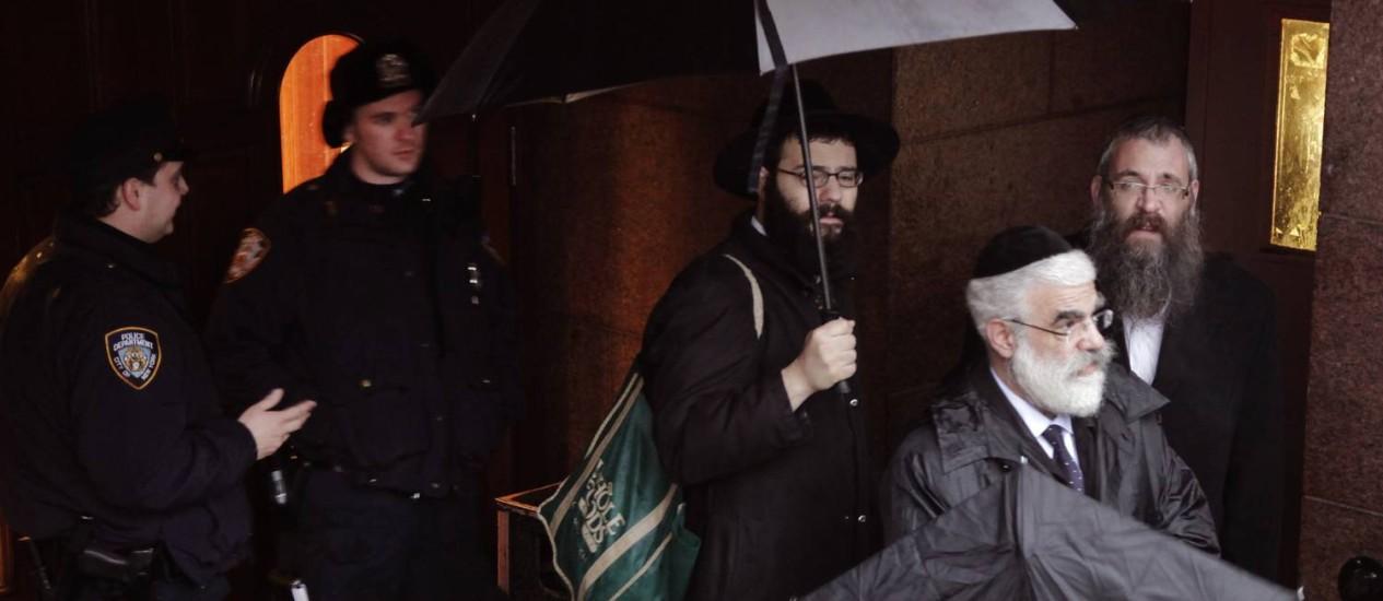 Membros da Chabad-Lubavitch saem do templo observados por policiais: tensão na madrugada Foto: Mark Lennihan / AP