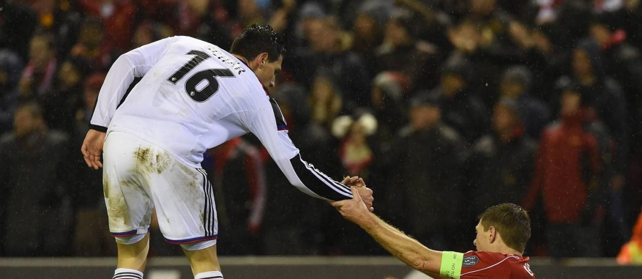 O zagueiro suíço Fabian Schaer estende a mão ao desolado capitão do Liverpool, Gerrard Foto: PAUL ELLIS / AFP