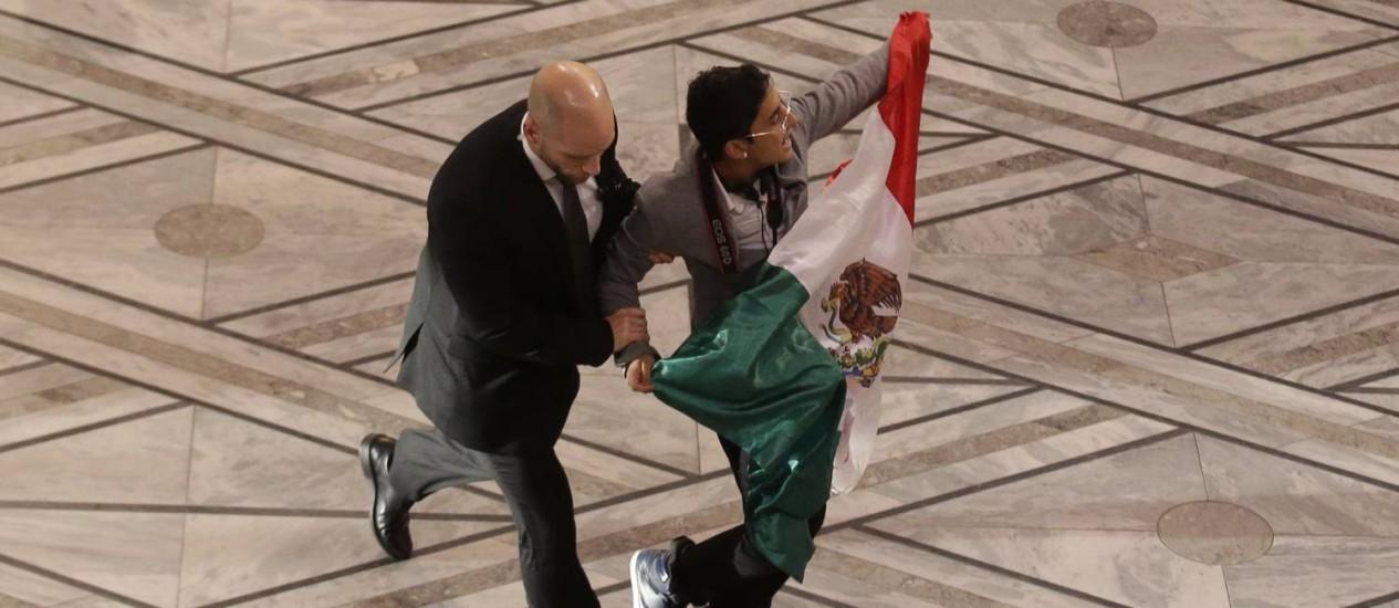 Manifestante com bandeira mexicana é escoltado por segurança na cerimônia de entrega do Prêmio Nobel Foto: Matt Dunham / AP