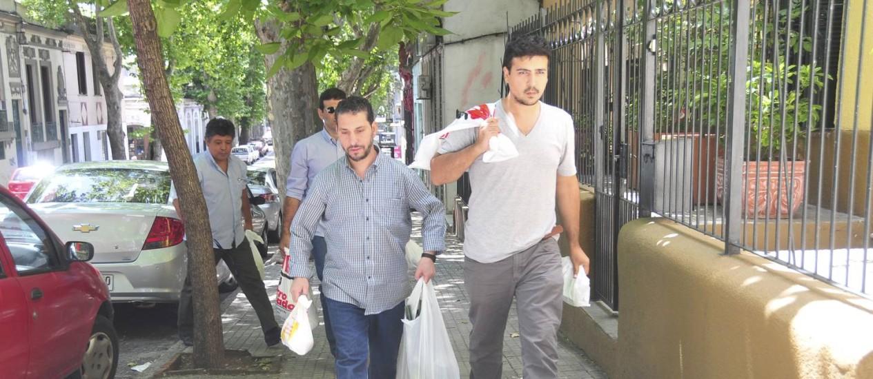 Dois ex-detentos de Guantánamo carregam sacola de compras acompanhados por um membro do sindicato dos trabalhadores do Uruguai PIT-CNT Foto: Ines Guimaraens / AP