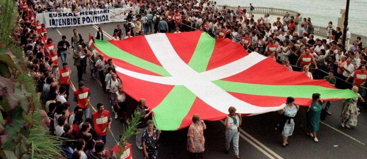 Apoiadores do partido nacionalista basco Herri Batasuna, braço político do ETA, carregam enorme bandeira nacional pelas ruas de San Sebastian em passeata de 1997. Membros do grupo foram condenados nesta sexta-feira por assaltos realizados na França Foto: Desmond Boylan / REUTERS