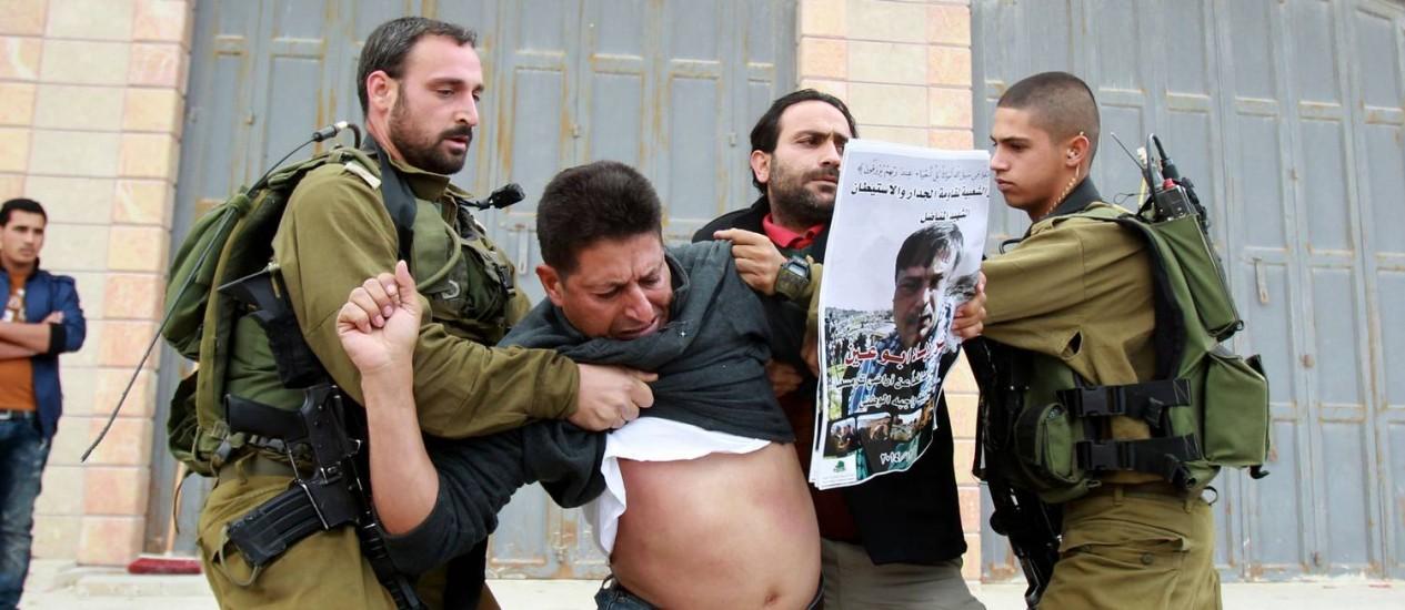 Soldados israelenses seguram dois palestinos que protestavam pela morte do ministro Ziad Abu Ein Foto: MUSA AL-SHAER / AFP