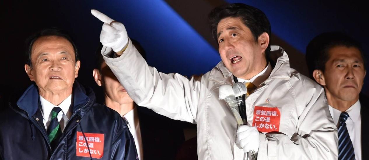 Primeiro-ministro japonês, Shinzo Abe (direita) durante comício de campanha. Partido Liberal Democrata não deve ter dificuldades para ampliar seu poder sobre o Parlamento nas novas eleições Foto: KAZUHIRO NOGI / AFP