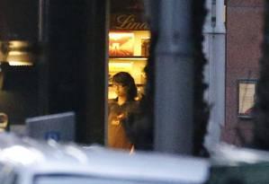 Mulher é vista da janela do Lindt Café, em Sydney, onde dezenas de pessoas são mantidas reféns Foto: DAVID GRAY / REUTERS