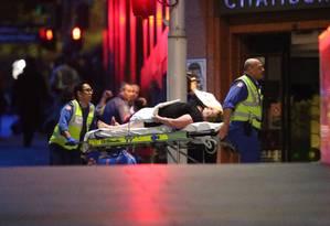 Uma mulher ferida é levada por paramédicos após ser liberada da cafeteria onde era mantida refém junto com um grupo de 40 pessoas Foto: Rob Griffith / AP