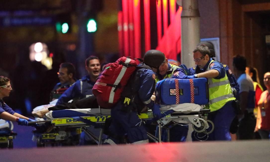 Uma das pessoas feridas no café de Sydney é carregada por paramédicos Foto: Rob Griffith / AP